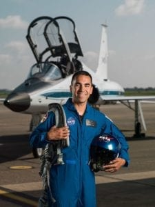 Raja Chari, Eagle Scout and member of 2017 NASA Astronaut Candidate Class, smiles in front of jet, wearing blue NASA flight suit.