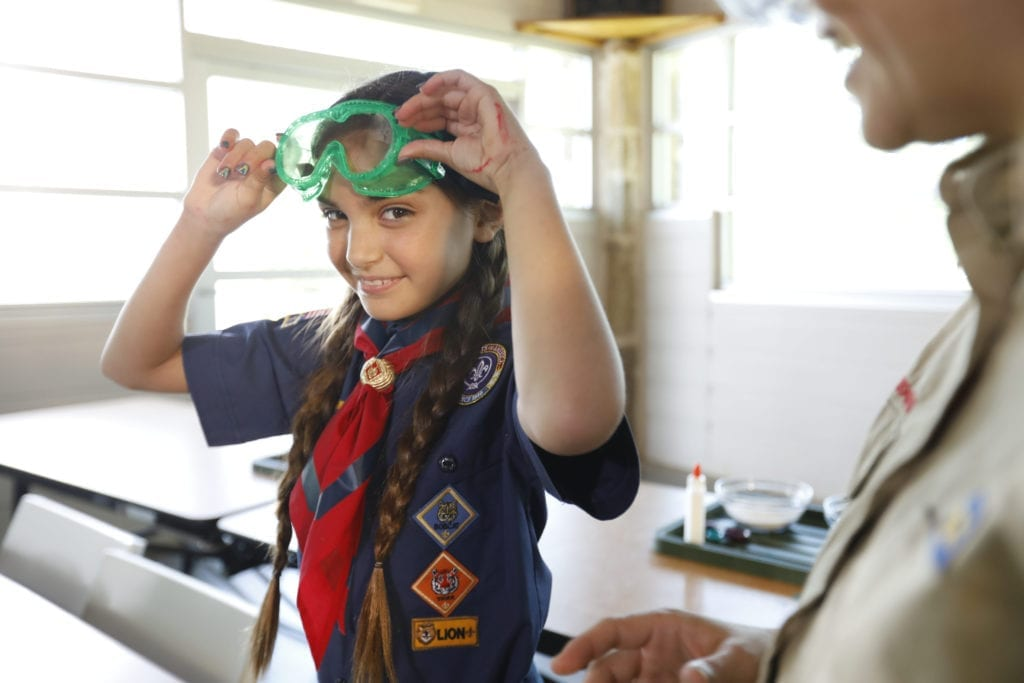 A girl with double braids in a Scouts BSA uniform smiles as she puts on lab goggles, ready to do a science experiment.