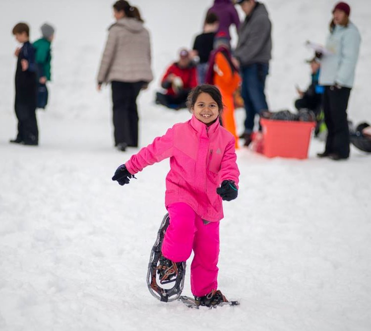 A young girl dressed in a bright pink snow suit smiles as she snow-shoes her way toward the camera.