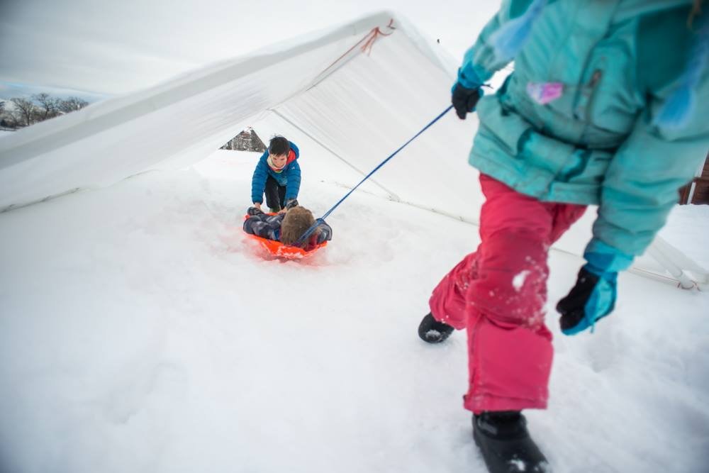 A girl in pink snow pants pulls a boy on an orange sled as they play outside in winter.