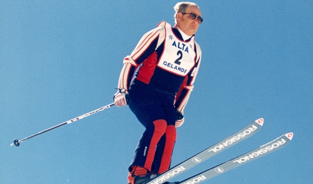 US Ski Hall of Fame athlete Alan Engen soars on a pair of skis, wearing red, white and blue snow suit and Alta bib.