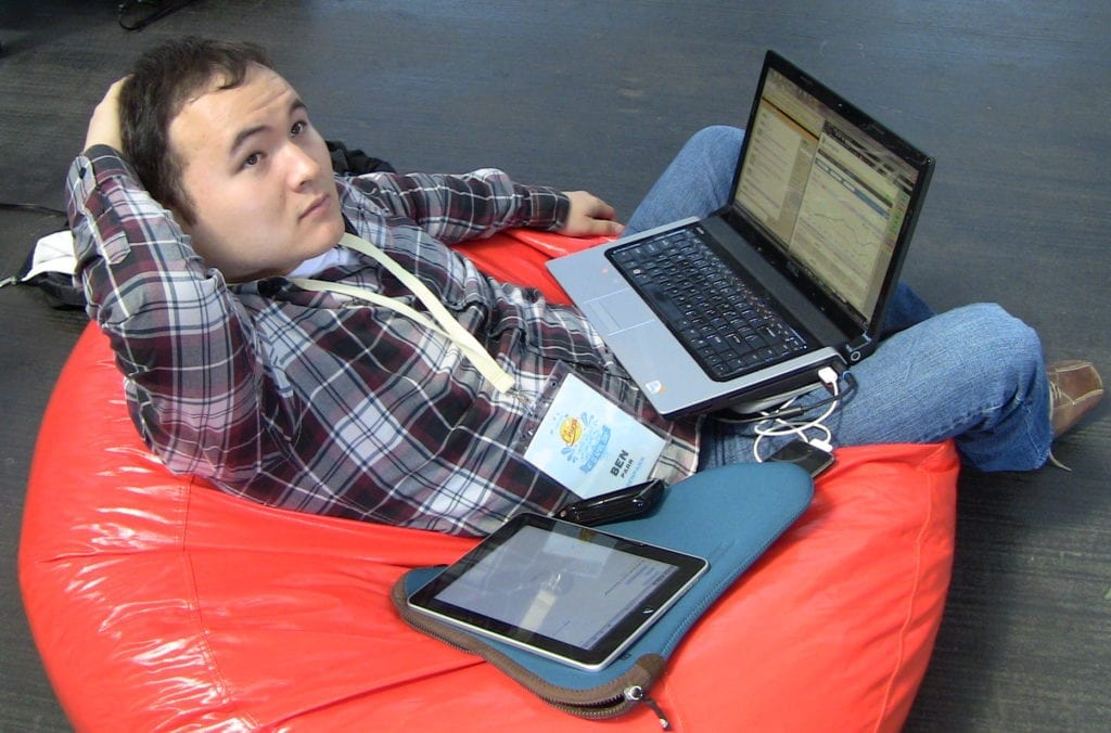 Ben Parr, at Chirp conference, sits in bean bag chair with laptop on lap.