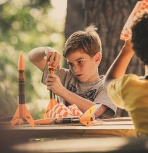 Two boys build rockets outside at a wooden picnic table, learning STEM skills.