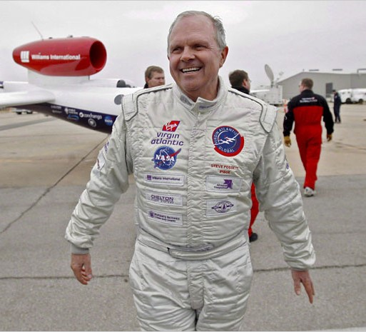 Steve Fossett walks in front of an aircraft, wearing white pilot's suit adorned with Virgin Atlantic and NASA logos. Fossett is an Eagle Scout.