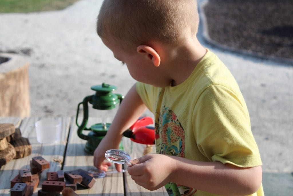 Young boy in yellow shirt learns STEM skills, playing outside with magnifying glass, building blocks and a green lantern.