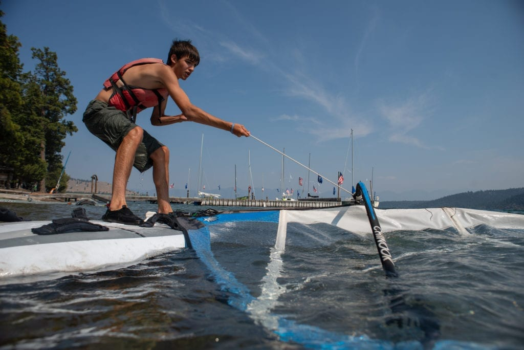 A Boy Scout pulls a windsurfing sail out of the water at summer camp, demonstrating independence and resilience.