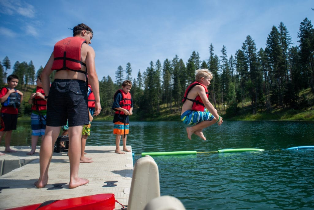 Boy Scout in lifevest cannon balls into a lake at summer camp, as other boys on dock watch.
