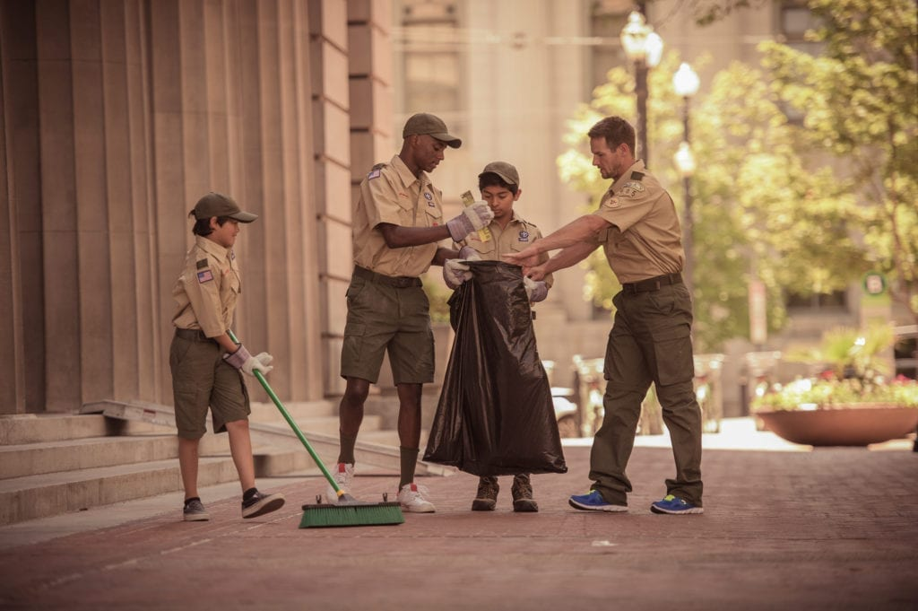 Three Scouts and a Scout Leader in uniform collect trash as community service in a large city.