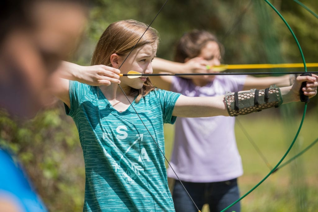 Two girls focus on targets while practicing archery at summer camp.