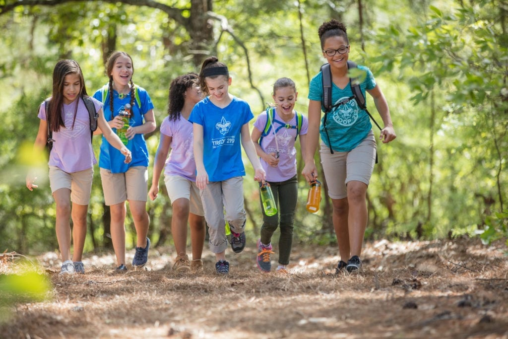 A group of girls participate in a Boy Scouts summer camp together, hiking in the wilderness.