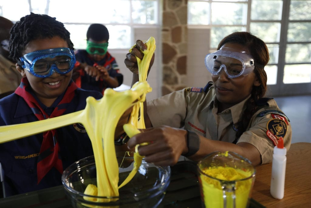 A boy and a girl wear safety goggles and stretch slime with their hands, practicing STEM skills at summer camp.