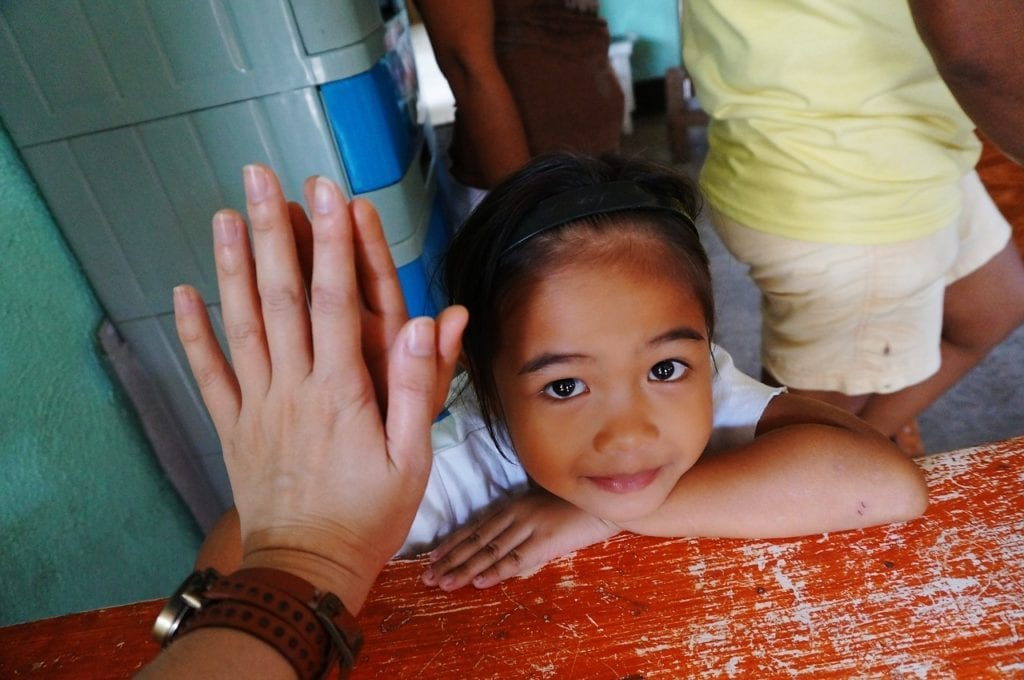 A small, cute girl looks up as she high-fives another volunteer.