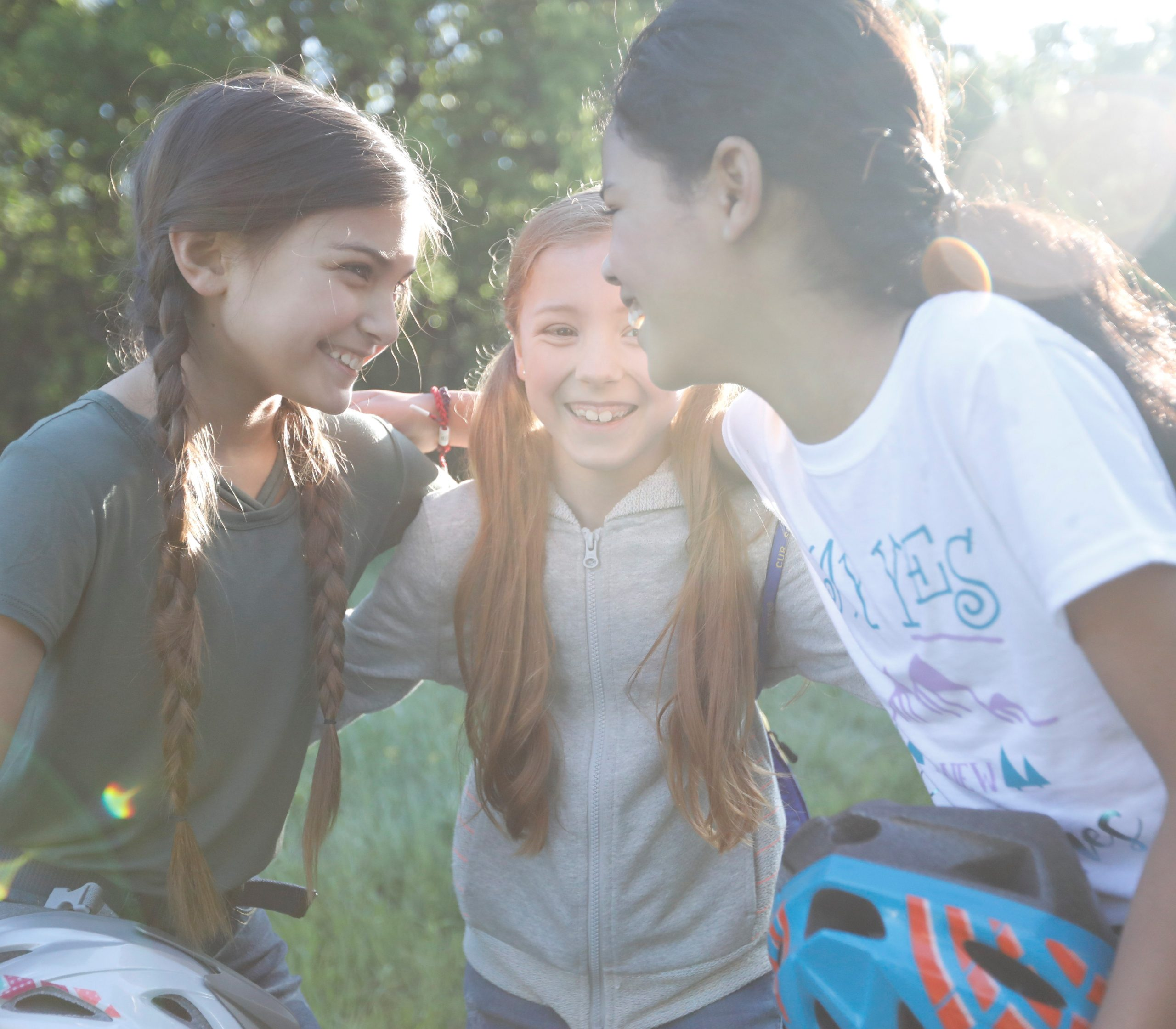 Three girls talking in a huddle after biking outside.