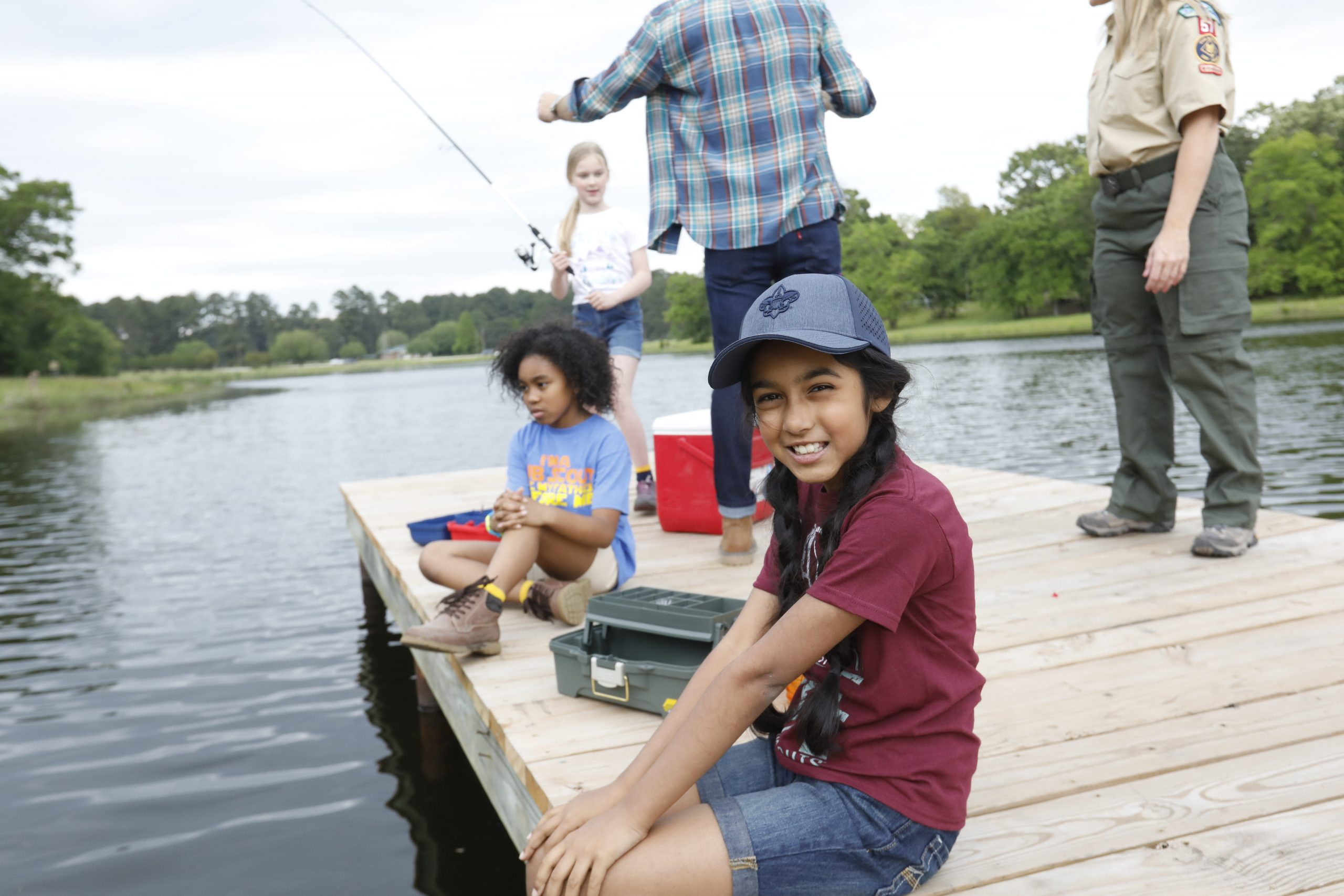 Girl wearing hat smiles as she sits on dock, fishing in lake at summer camp.
