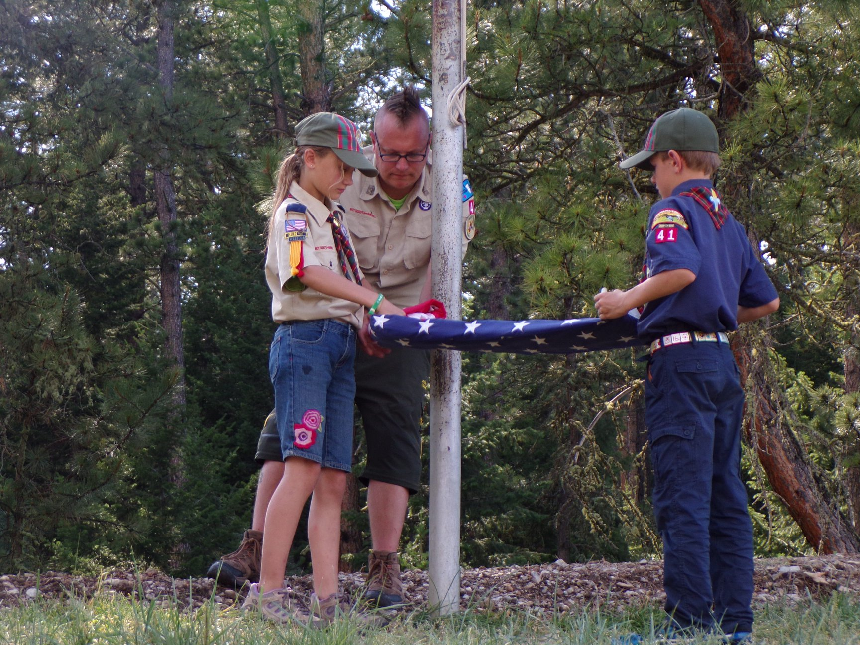 Two Scouts in uniform properly fold an American flag at summer camp.