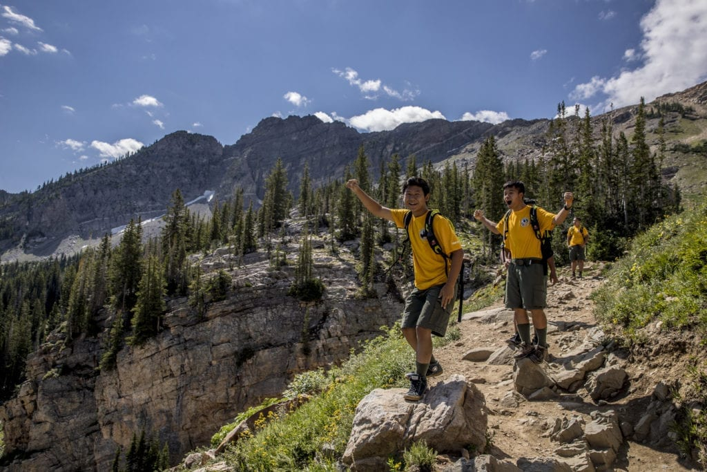 Two boys cheer as they reach the top of a mountain after a long and beautiful hike with friends.