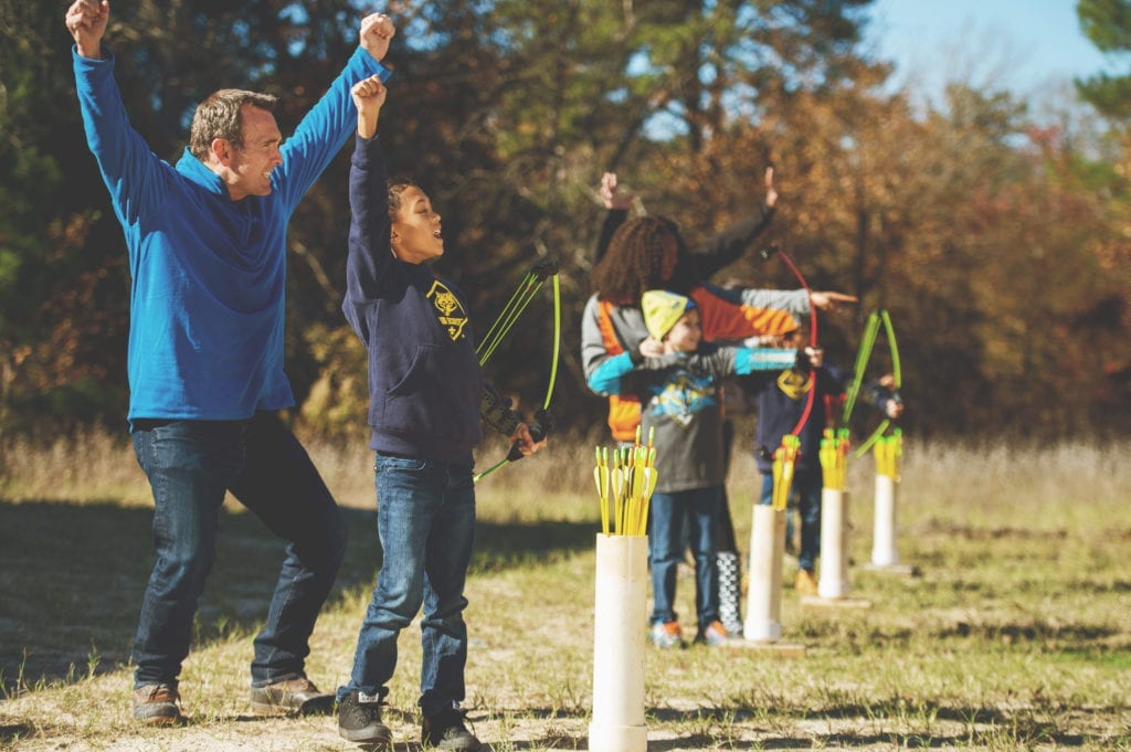 Scout and troop leader cheer as boy hits bullseye in archery.