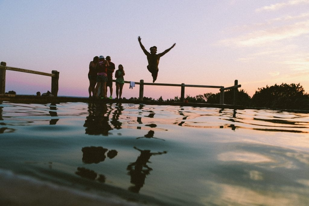 Boy jumping into lake, as others watch from dock and sun sets.