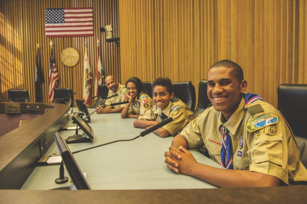 Group of older kids in Scouts BSA uniforms sit at microphones in a city council meeting.