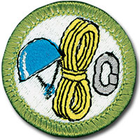 Rock climbing merit badge for Boy Scouts, featuring rope, helmet and carabiner