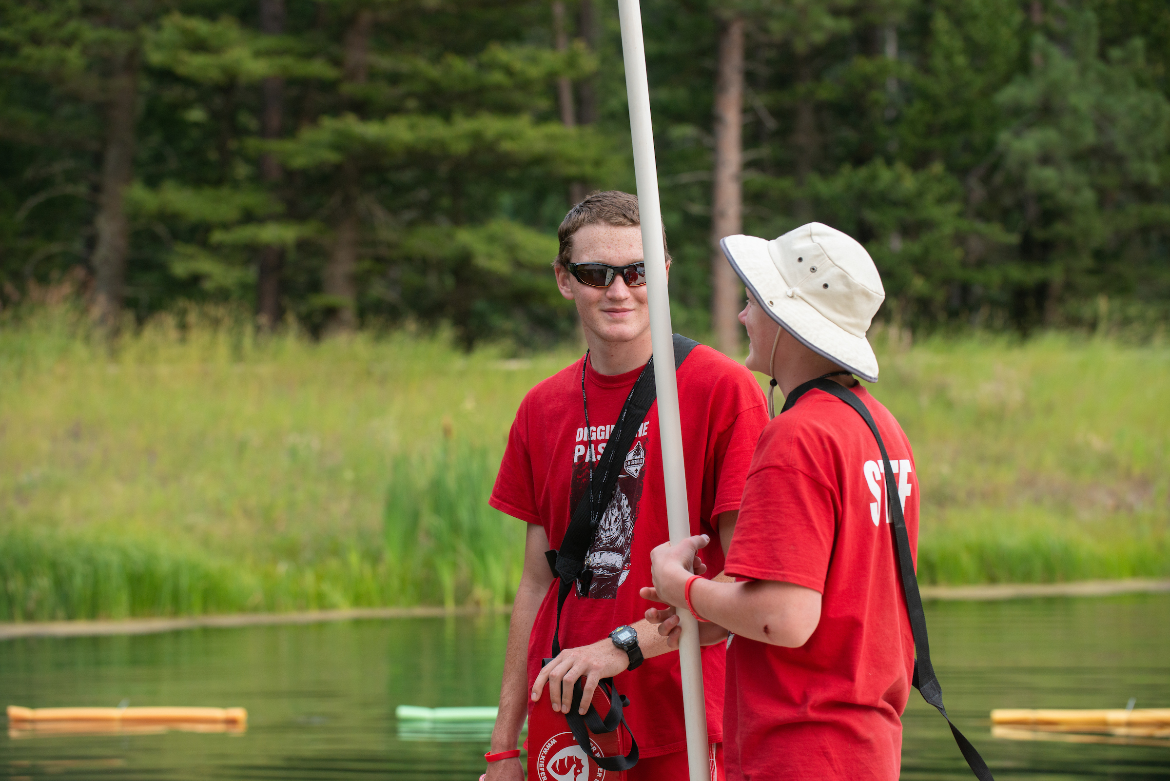 Two camp counselors in red t-shirts talk to each other on a dock