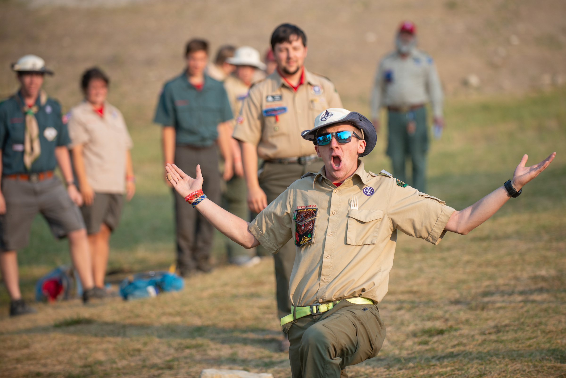 Boy Scouts camp counselor speaks enthusiastically to a group at summer camp