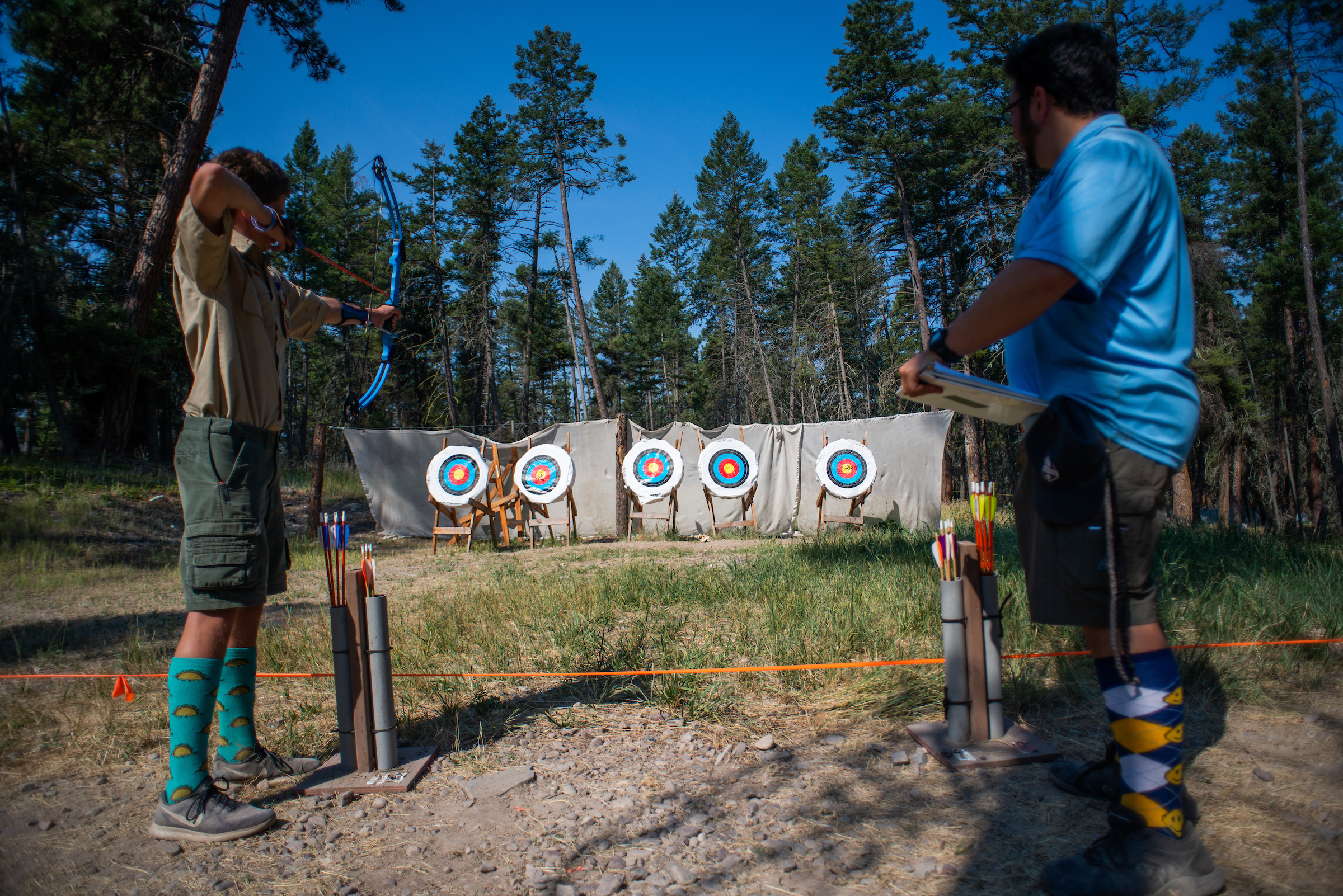 Camp counselor teaches Boy Scout archery at summer camp