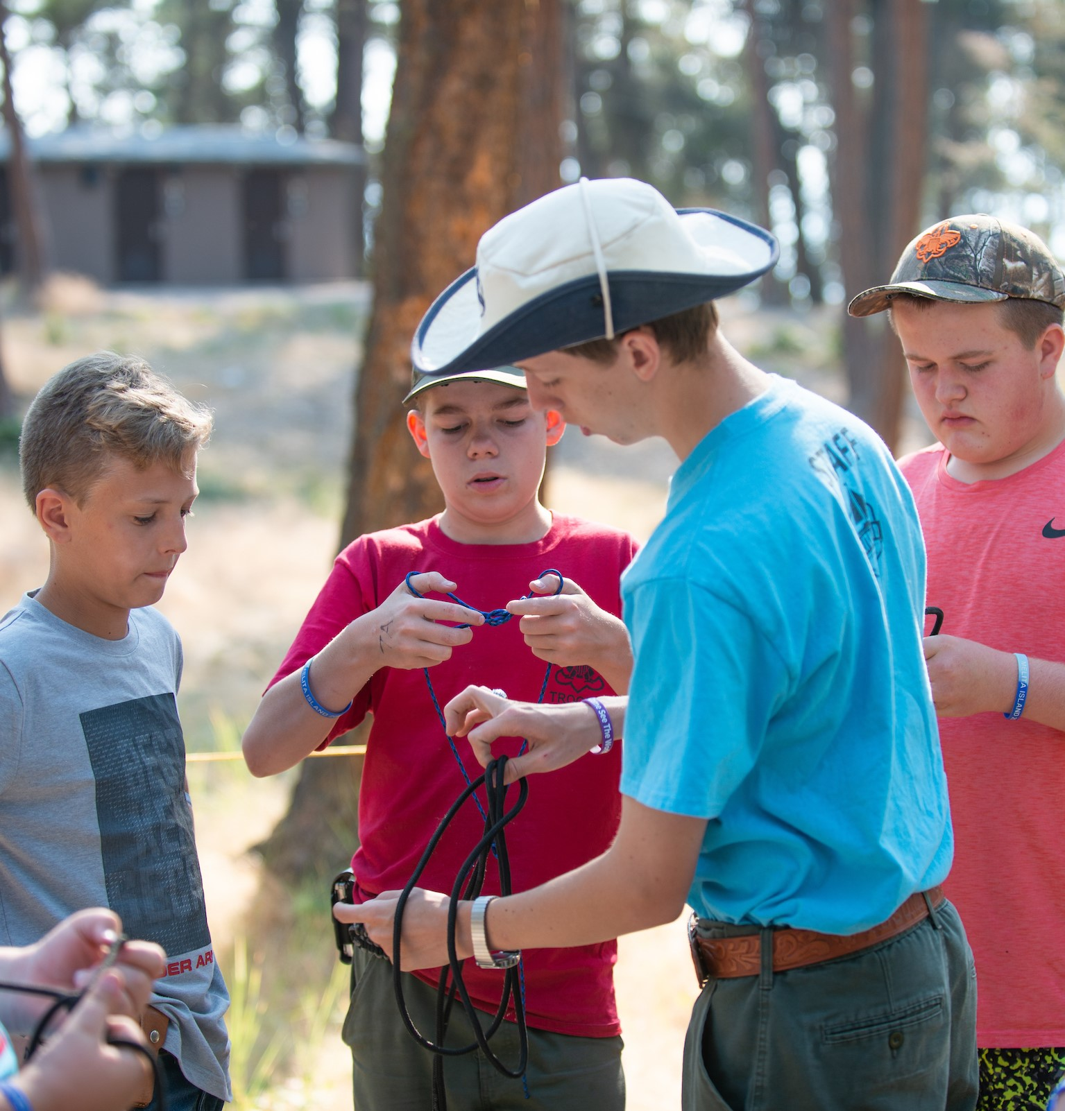 Summer camp staff teaches group of Boy Scouts how to tie a knot